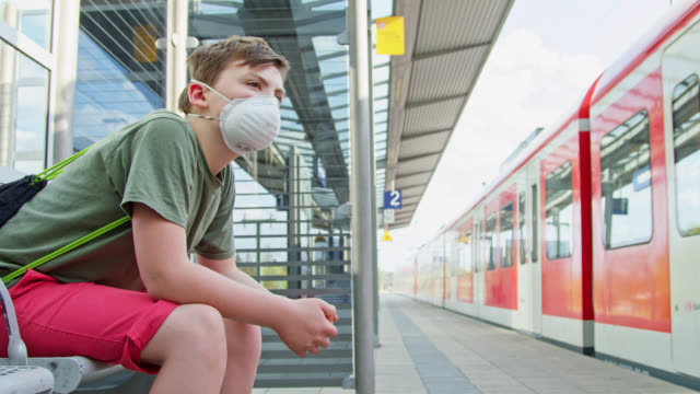 schoolboy is wearing a protective ffp-2 mask to prevent from contagious virus while waiting at train station and a suburban train is leaving. - day in the life stock videos & royalty-free footage