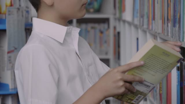 schoolboy keeping book on shelf in library - neugierde stock-videos und b-roll-filmmaterial