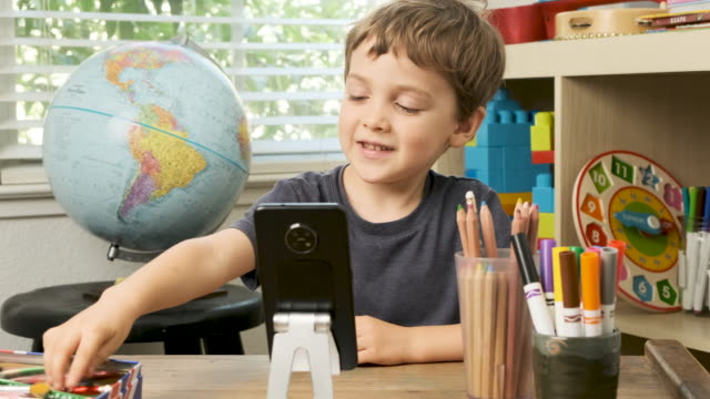 schoolboy talking to his teacher using a smart phone sitting at his room desk - remote location phone stock videos & royalty-free footage