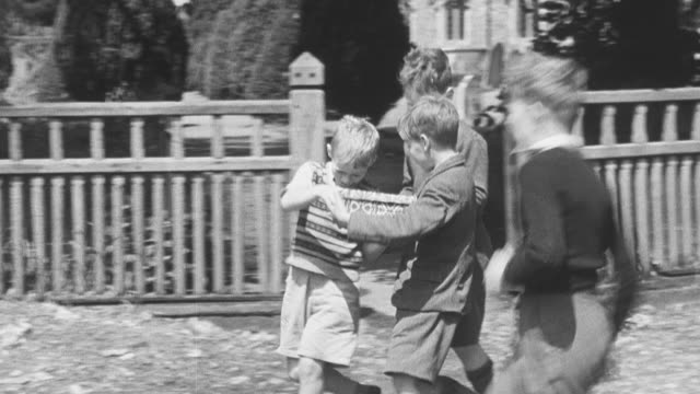 vidéos et rushes de 1950 ts a schoolboy walking along the sidewalk carrying a box gathering the attention of fellow schoolboys resulting in them huddling around him observing the contents of the box as they continue walking along / united kingdom - boîte