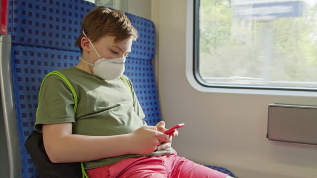 schoolboy wearing ffp-2 protective mask gaming on phone while travelling in suburban rain. - public transportation stock videos & royalty-free footage