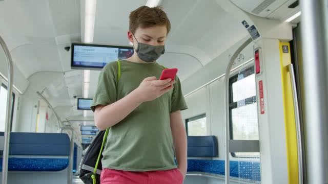 schoolboy wearing protective diy face mask with smart phone alone in empty suburban train. - männlicher teenager stock-videos und b-roll-filmmaterial