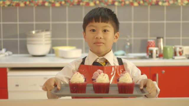 vidéos et rushes de schoolboy with cupcake - groupe moyen d'objets