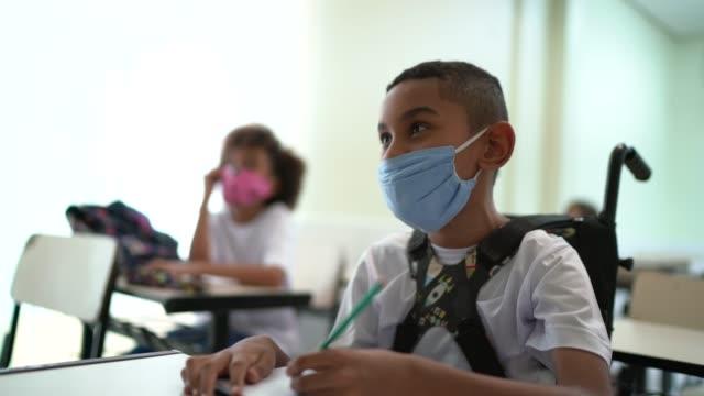 vídeos de stock, filmes e b-roll de estudante com deficiência usando máscara facial estudando na escola - escola