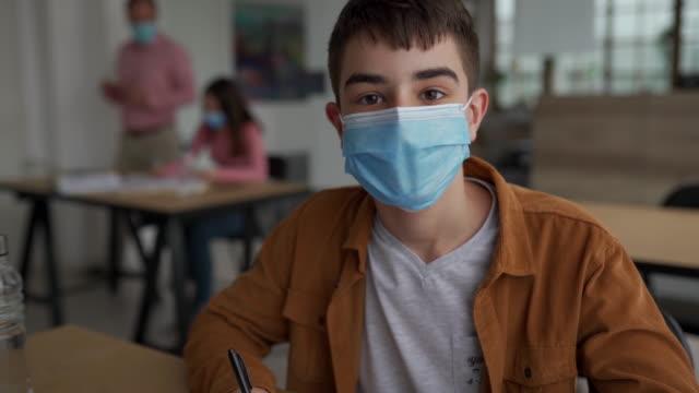 vídeos de stock e filmes b-roll de schoolboy with protective face mask at classroom - 12 13 anos