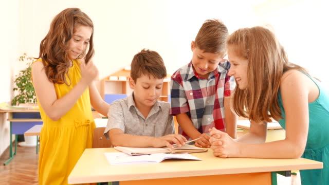 Schoolboys and schoolgirls having fun in classroom