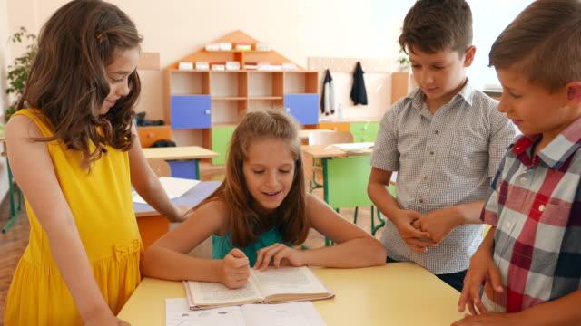 schoolboys and schoolgirls in classroom - libro di testo video stock e b–roll