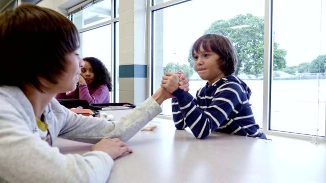 vídeos de stock e filmes b-roll de schoolboys arm wrestle during lunch in school cafeteria - aluna da escola secundária