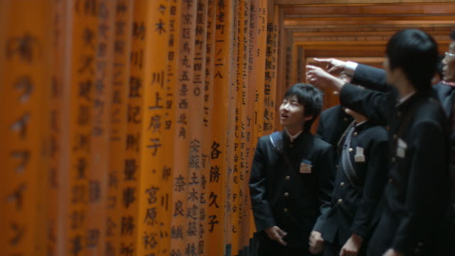 ms pan schoolboys in uniforms looking at text in torii gates leading to inner fushimi inari taisha shrine, kyoto, japan - uniforme scolastica giapponese video stock e b–roll