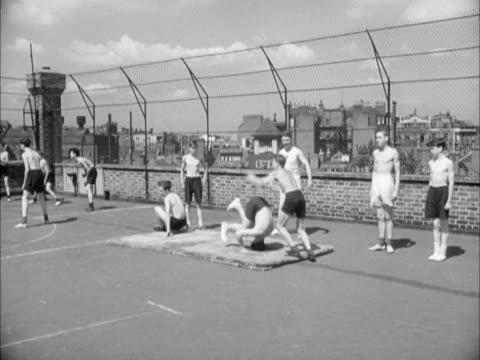 vídeos y material grabado en eventos de stock de schoolboys take part in a pe lesson on a rooftop playground - niño en edad escolar