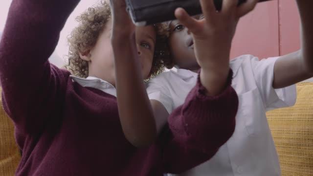 schoolboys taking selfie through digital tablet - schulkind nur jungen stock-videos und b-roll-filmmaterial