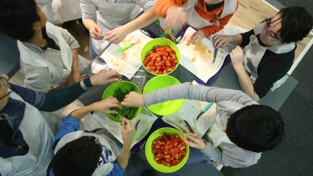 schoolchildren cut tomatoes for a salad at a mini cooking class at the 2018 international green week agricultural trade fair on january 19 2018 in... - tradeshow stock videos and b-roll footage