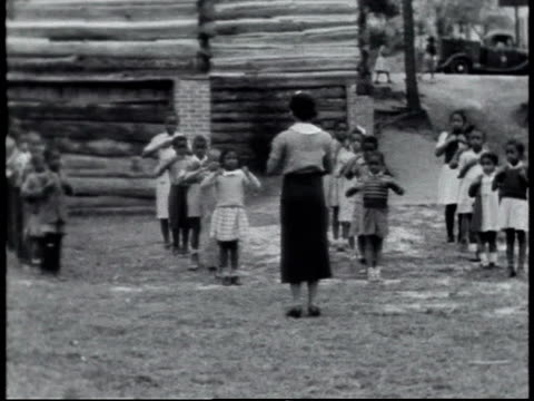 1940 MONTAGE schoolchildren doing calisthenics in schoolyard / Alabama, United States