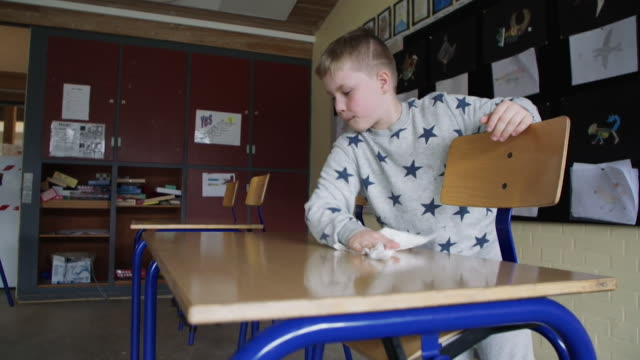 """schoolchildren helping to disinfect the classroom at primary school in denmark after it reopened after coronavirus lockdown restrictions were lifted - """"bbc news"""" stock videos & royalty-free footage"""