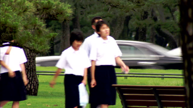 Schoolchildren in uniforms walk through a park, Japan. Available in HD.