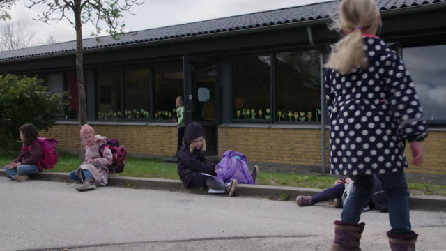 """schoolchildren sat apart outside primary school in denmark as they observe social distancing after it reopened after coronavirus lockdown was lifted - """"bbc news"""" stock videos & royalty-free footage"""