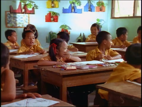 Schoolchildren sitting at desks + laughing in classroom / stand up + start singing / Bali