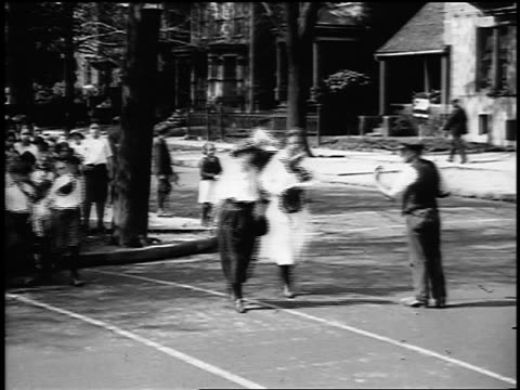 b/w 1915 schoolchildren with teachers crossing street with crossing guard helping them / newsreel - newsreel stock videos and b-roll footage
