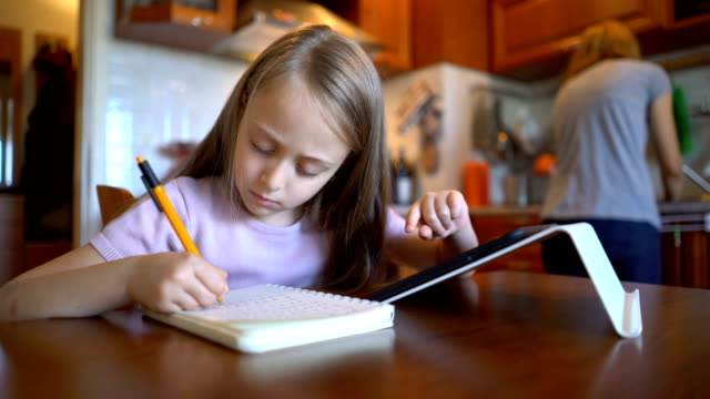Schoolgirl browsing on her tablet at home and writing down in a notebook