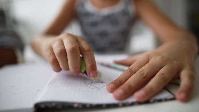 自宅で宿題のためのノートパッドに鉛筆で描く女子高生 - 消しゴム点の映像素材/bロール