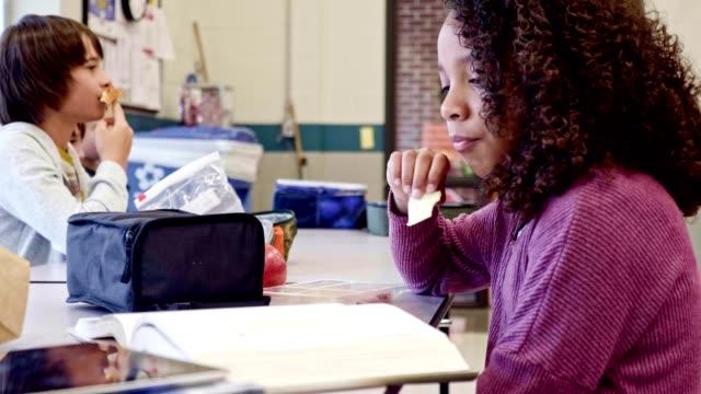 schoolgirl eats lunch alone in school cafeteria - snack stock videos & royalty-free footage
