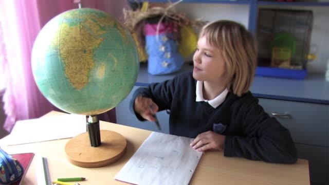 vídeos de stock e filmes b-roll de aluna homeworking - globo terrestre de escritório