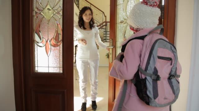 ms schoolgirl knocking on door and hugging mother / china - 建物入口点の映像素材/bロール