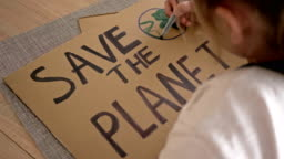 Schoolgirl makes a poster SAVE THE PLANET