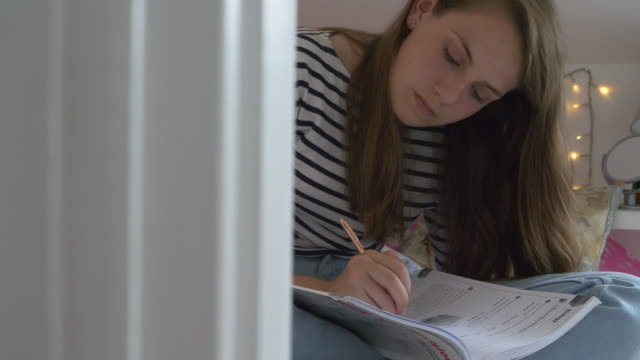 Schoolgirl makes homework in her bedroom.