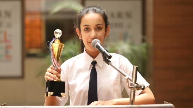 schoolgirl raising trophy and giving speech at awards ceremony - award stock videos & royalty-free footage
