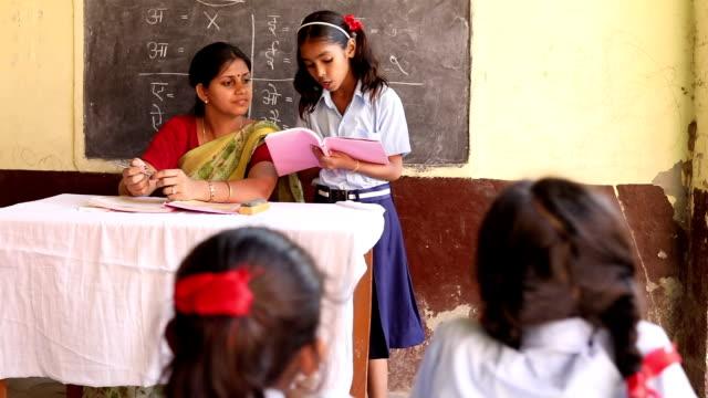 vídeos de stock e filmes b-roll de schoolgirl reading a book in classroom, haryana, india - professora