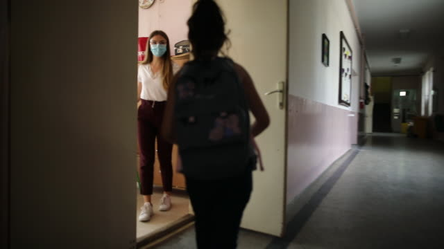 schoolgirl running down hallway because she's running late for class while teacher holding door open for her to get in classroom - corridor stock videos & royalty-free footage