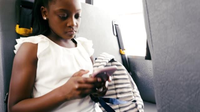 schoolgirl uses smartphone on school bus - bubble gum stock videos & royalty-free footage
