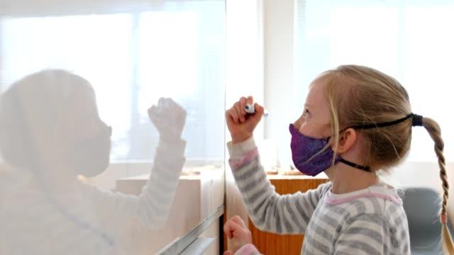 vidéos et rushes de écolière avec le masque de visage faisant le travail d'école - enfant d'âge scolaire