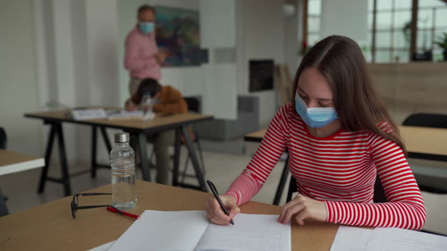 schoolgirl with protective face mask at classroom - educazione video stock e b–roll