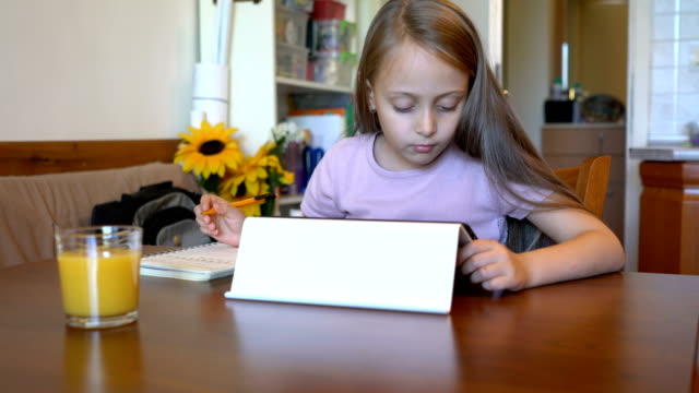 schoolgirl writing down in her notepad and checking on the tablet - learning disability stock videos & royalty-free footage
