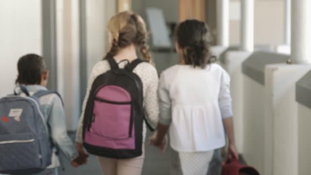 vídeos de stock, filmes e b-roll de schoolgirls entering classroom in school building - vista traseira