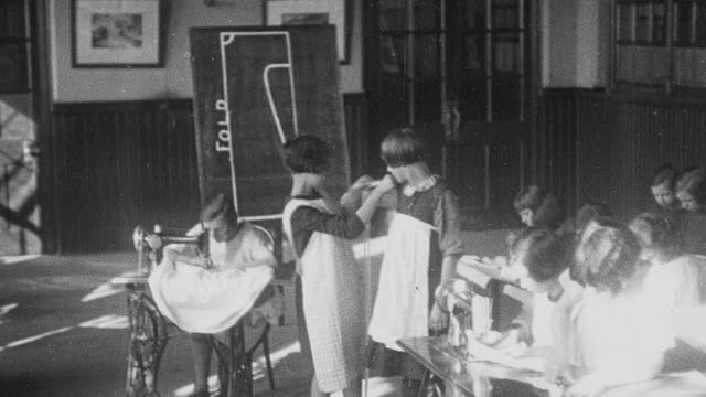 1925 montage schoolgirls in home economics class with student measuring fellow student, students operating sewing machines, cutting out patterns, and holding up finished garments / newcastle upon tyne, england, united kingdom - home economics class stock videos & royalty-free footage