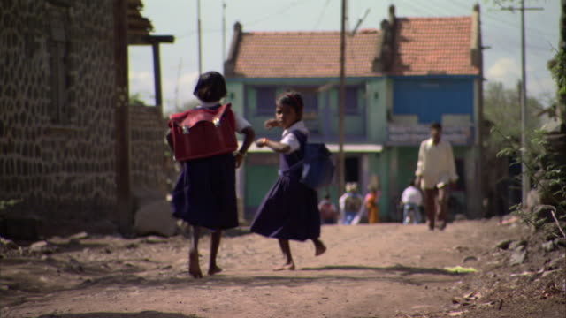 WS Schoolgirls in uniform with backpacks running away down dirt road in poor village, Pune, Maharashtra, India