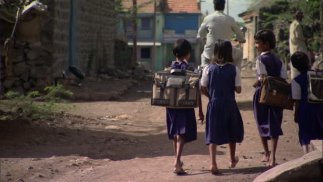 vídeos y material grabado en eventos de stock de ms schoolgirls in uniforms with backpacks walking away down dirt road in poor village, pune, maharashtra, india - asiático e indio