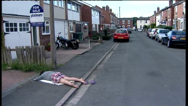 schoolgirl's 'playing dead' prank alerts google street view viewers england worcestershire worcester ext azura beebbeejaun lies on pavement in... - enacting stock videos & royalty-free footage