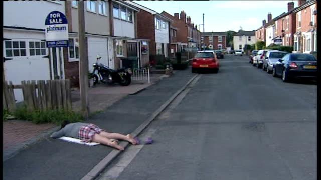 schoolgirl's 'playing dead' prank alerts google street view viewers azura beebbeejaun lies on pavement in suburban street - enacting stock videos & royalty-free footage