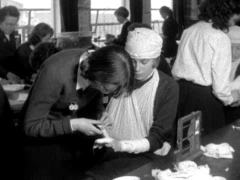 vidéos et rushes de schoolgirls practice bandaging during a first aid lesson 1958 - pansement médical