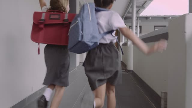 schoolgirls running towards classroom - educazione video stock e b–roll