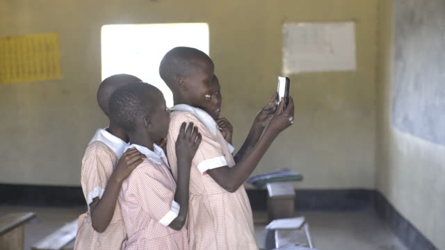 Schoolgirls using computer tablet. Kenya, Africa.