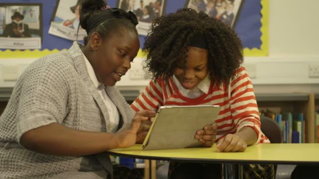 Schoolgirls using tablet