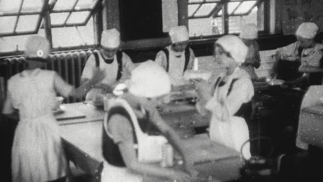 1925 montage schoolgirls wearing caps and aprons preparing and cooking food and setting a dining table in home economics class / newcastle upon tyne, england, united kingdom - home economics class stock videos & royalty-free footage