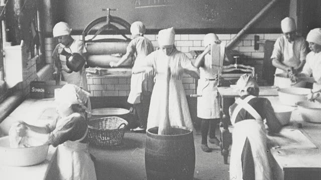 1925 montage schoolgirls wearing caps and aprons washing clothes using a mangle wringer machine, barrel and paddle, ironing, and hanging washing on outdoor clothesline in home economics class / newcastle upon tyne, england, united kingdom - home economics class stock videos & royalty-free footage