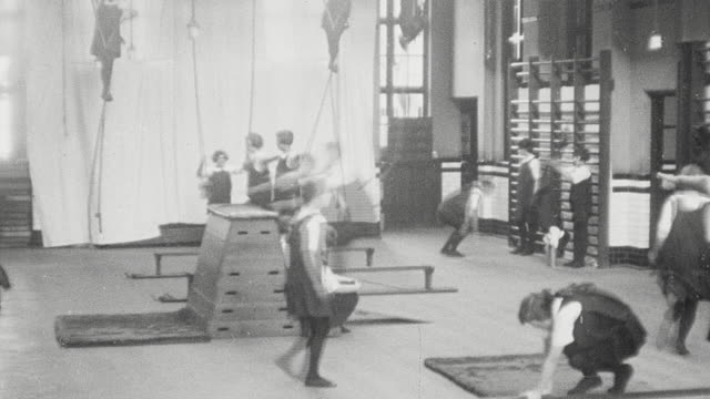 vidéos et rushes de 1925 montage schoolgirls wearing gymslips engaged in gymnastics, climbing ropes and bars, vaulting, tumbling, and doing handstands in gym at secondary school / newcastle upon tyne, england, united kingdom - angleterre