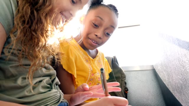 schoolgirls work on homework assignment while on schoolbus - back to school stock videos & royalty-free footage